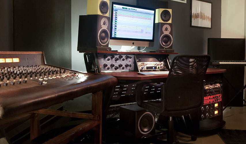 Studio control room with an analog console, analog gear, speakers, and a DAW on the screen.